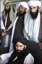 Afghan Ambassador to Pakistan Abdul Salam Zaeef seated in front of Taliban militia members. Source/AP Photos